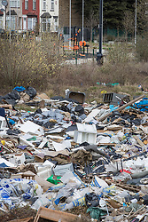 © Licensed to London News Pictures. 29/03/2018. London, UK. A large pile of waste and rubbish has been dumped in an area of scrap land next to houses, and here a recreation park (top),  in Edmonton, north London. Local residents are calling it a 'river of rubbish' and say it has been there for a month and are campaigning for it's removal.  Photo credit: Peter Macdiarmid/LNP