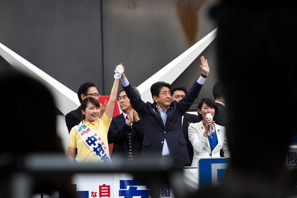TOKYO, JAPAN - JULY 1: Japanese Prime Minister Shinzo Abe, president of the ruling Liberal Democratic Party and his party candidate Aya Nakamura waves their hands to voters from atop of a campaign van with party's members during election campaign for Tokyo Metropolitan Assembly on July 1, 2017 in Akihabara, Tokyo, Japan. (Photo: Richard Atrero de Guzman/NUR Photo)