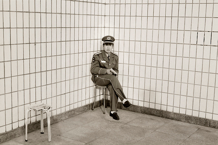 A subway security guard in Beijing wakes from a nap.