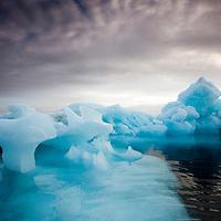 Norway, Svalbard, Nordaustlandet, Morning sun lights melting sea ice along Wahlberg Island on summer morning
