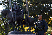 An officer looks on while workers remove a statue of Robert E. Lee from a public park in Dallas, Thursday, Sept. 14, 2017. (Cooper Neill for The Texas Tribune)