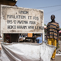 A sign in the center of Bosso calls the population to collaborate with the authorities in order to fight against Boko Haram. Many insurgents hide among the civilian population, making it difficult to maintain security for the Defense Forces and Multinational Security.<br /> <br /> The conflict and the resulting lack of security have caused the local economy to crash and severely hampered cross-border trade, fishing, irrigated agriculture and nomadic herding. In an area where climatic conditions are already precarious and options limited, people are turning increasingly to aid. In Bosso alone, the ICRC is providing almost 25,000 people &ndash; nearly a third of the population &ndash; with emergency food aid every month.