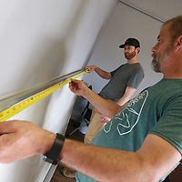 Colby Cuevas, left, and Chris Clark measure for the center of a whiteboard before they hang it  in the new BLAST space at the Autism Center in Tupelo.