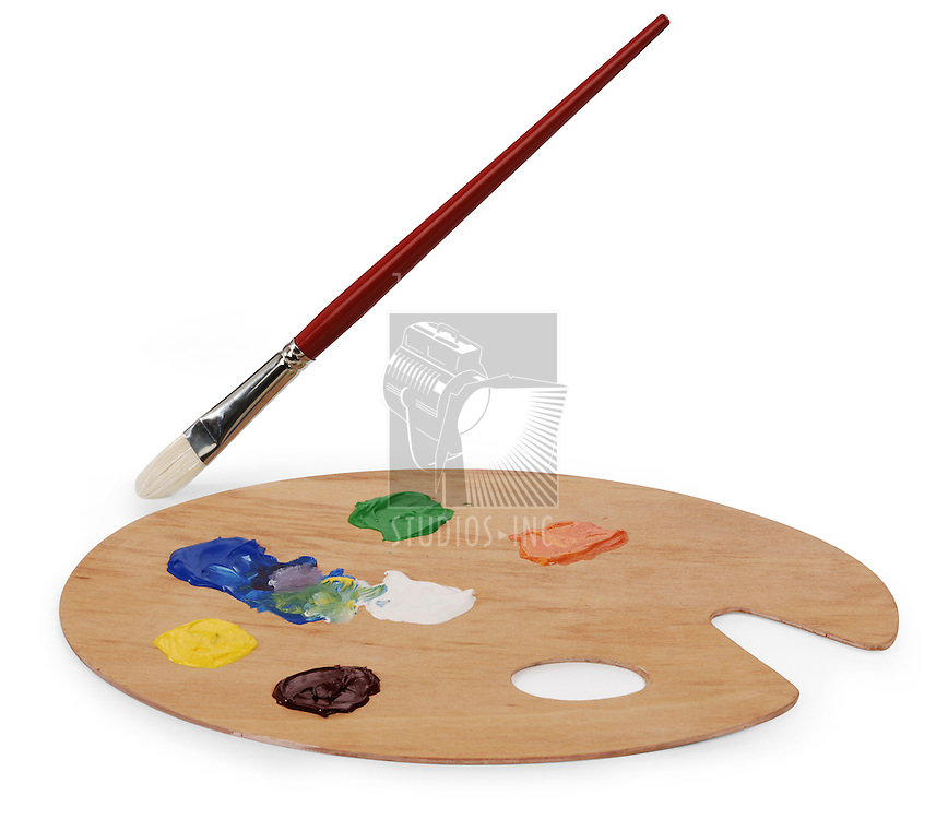wooden art palette with blobs of paint and a brush on white background with clipping path. Shot at an angle with brush separated for animation
