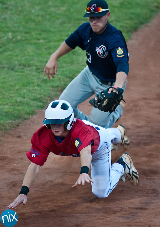 Concord Post 51's Blaine Hill chases down Mooresville Post 66's  Jesse Seaford as he tries to get back to first base Friday night at Lake Norman High School. Mooresville won the game 5-2. (Photo by James Nix)