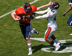 Virginia quarterback Brendon Lane (13) delivers a stiff arm to Virginia cornerback Devin Wallace (42).  The Virginia Cavaliers football team played the annual spring football scrimmage at Scott Stadium on the Grounds of the University of Virginia in Charlottesville, VA on April 18, 2009.  (Special to the Daily Progress / Jason O. Watson)