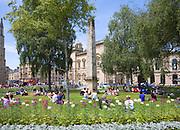 People enjoying summer sunshine on the grass at Orange Grove, Bath, Somerset, England