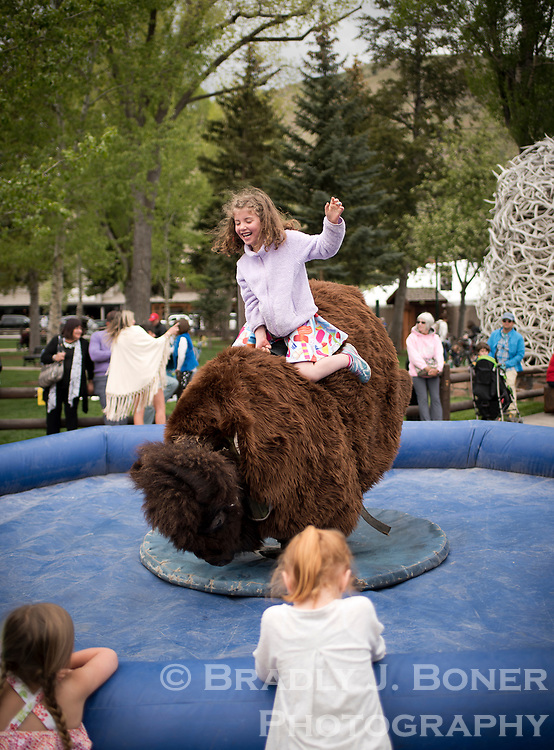 Vivian Daus, 6, takes on the mechanical bison while enjoying Old West Days festivities Saturday at the Jackson Town Square.