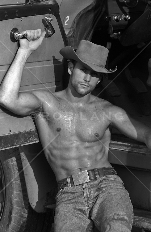 handsome cowboy outdoors without a shirt holding a car door handle