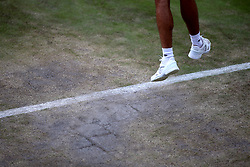 General view of the wear and tear to the grass on the baseline of court three on day eight of the Wimbledon Championships at The All England Lawn Tennis and Croquet Club, Wimbledon.