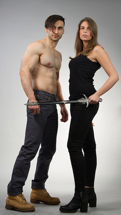 Couple posing together in contemporary outfits.