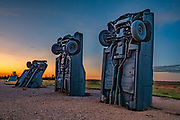 """Carhenge sunrise. Carhenge replicates England's Stonehenge using vintage American automobiles, near Alliance, Nebraska, in the High Plains region, USA. After studying Stonehenge in England, years later, Jim Reinders recreated the physical size and placement of Stonehenge's standing stones in summer 1987, helped by 35 family members. Reinders said, """"It took a lot of blood, sweat, and beers."""" Carhenge was built as a memorial to Reinders' father. 39 automobiles were arranged in the same proportions as Stonehenge with the circle measuring a slightly smaller 96 feet (29m) in diameter. Some autos are held upright in pits five feet deep, trunk end down, while other cars are placed to form the arches and welded in place. All are covered with gray spray paint. The heel stone is a 1962 Cadillac. Reinders donated Carhenge to the Friends of Carhenge, who gifted it to the Citizens of Alliance in 2013. Additional sculptures have been erected in the Car Art Reserve, where Reinders' """"Ford Seasons"""" is comprised of four Fords, inspired by Vivaldi's Four Seasons. Also, 29-year-old Canadian Geoff Sandhurst sculpted a spawning salmon."""
