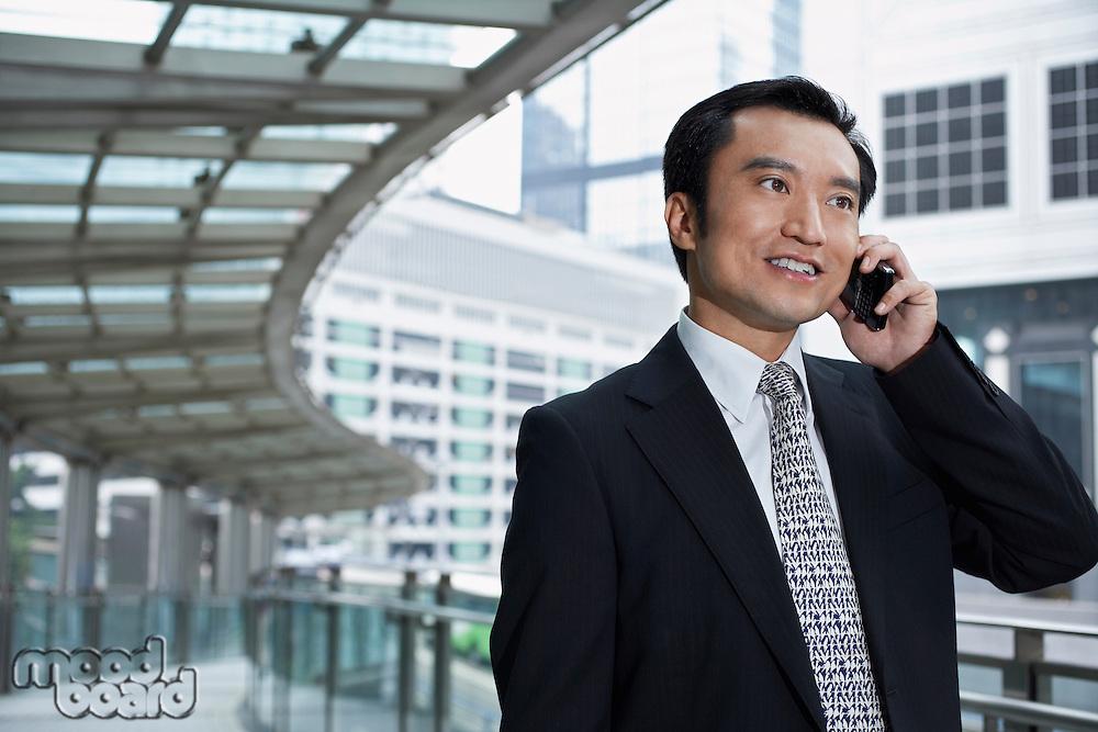 China Hong Kong business man using mobile phone standing on footbridge