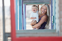 Young mother holding son (1-2) on outdoor porch portrait