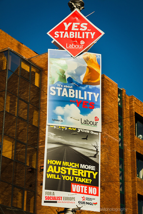 "May 2012, Dublin Ireland: A Collection of posters supporting both the yes and no sides in the upcoming referendum on the european fiscal treaty. The streetlight nearest the camera includes two posters in support of the treaty, from the Labour party which contain the message ""yes for stability"". There is also one in support of the No capmaign by the socialist party"