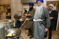 High Priest and members of the Sikh Community preparing a meal to celebrate Guru Nanak's Birthday,