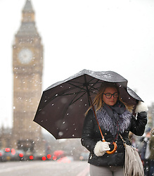 © Licensed to London News Pictures. 13/01/2017. London, UK. People walk across Westminster Bridge whilst snowing in London on Friday, 13 January 2017. Photo credit: Tolga Akmen/LNP