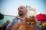 A man holding a pomeranian dog during Yappy Hour at the Wonder Bar in Asbury Park, New Jersey
