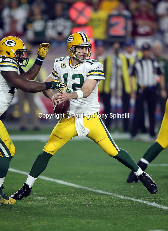 Green Bay Packers quarterback Aaron Rodgers (12) fakes a handoff to Green Bay Packers running back Eddie Lacy (27) during the NFL NFC Divisional round playoff football game against the Arizona Cardinals on Saturday, Jan. 16, 2016 in Glendale, Ariz. The Cardinals won the game in overtime 26-20. (©Paul Anthony Spinelli)