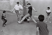 Friends play football with local kids in car park, Southall, UK, 1987.