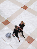 Two business women walking with suitcase elevated view long exposure