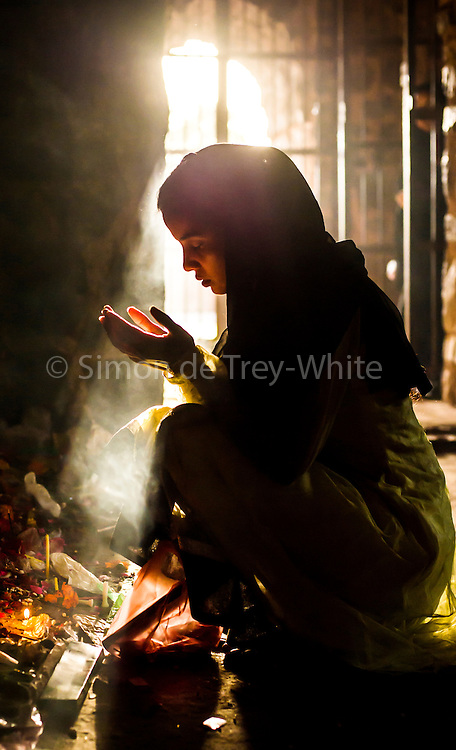 9th April 2015, New Delhi, India. Women pray at a shrine dedicated to Djinn worship in the ruins of Feroz Shah Kotla in New Delhi, India on the 9th April 2015<br /> <br /> PHOTOGRAPH BY AND COPYRIGHT OF SIMON DE TREY-WHITE a photographer in delhi<br /> + 91 98103 99809. Email: simon@simondetreywhite.com<br /> <br /> People have been coming to Firoz Shah Kotla to leave written notes and offerings for Djinns in the hopes of getting wishes granted since the late 1970's. Jinn, jann or djinn are supernatural creatures in Islamic mythology as well as pre-Islamic Arabian mythology. They are mentioned frequently in the Quran  and other Islamic texts and inhabit an unseen world called Djinnestan. In Islamic theology jinn are said to be creatures with free will, made from smokeless fire by Allah as humans were made of clay, among other things. According to the Quran, jinn have free will, and Iblīs abused this freedom in front of Allah by refusing to bow to Adam when Allah ordered angels and jinn to do so. For disobeying Allah, Iblīs was expelled from Paradise and called &quot;Shayṭān&quot; (Satan).They are usually invisible to humans, but humans do appear clearly to jinn, as they can possess them. Like humans, jinn will also be judged on the Day of Judgment and will be sent to Paradise or Hell according to their deeds. Feroz Shah Tughlaq (r. 1351&ndash;88), the Sultan of Delhi, established the fortified city of Ferozabad in 1354, as the new capital of the Delhi Sultanate, and included in it the site of the present Feroz Shah Kotla. Kotla literally means fortress or citadel.