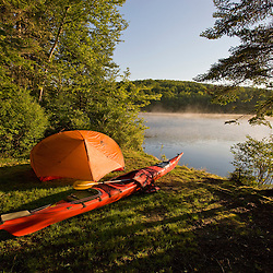 A kayak and a tent next to the Androscoggin River at a remote campsite at Mollidgewock State Park in Errol, New Hampshire.