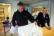 A woman guard (right) is assisting an inmate (centre) while working in the laundry room of the luxurious Halden Fengsel, (prison) near Oslo, Norway.