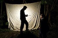 IFTE-NB-007554; Niall Benvie; Entomologist examining moths attracted to lamp; Austria; human; Homo; sapiens; Europe; Austria; Tirol; Fliesser Sonnenhänge; people person; horizontal; white black green; male man; adult; three; upland meadow grassland woodland edge; 2008; July; summer; night; artificial; Wild Wonders of Europe Naturpark Kaunergrat