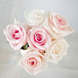 Overhead view of a rose bouquet on table with white linen.