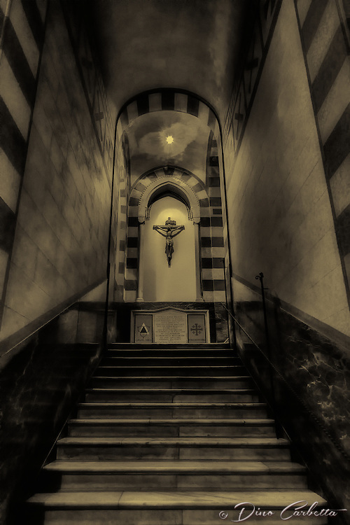 &ldquo;Climb to Christ - St. Andrew Cathedral of Amalfi - BW&rdquo;&hellip;<br /> <br /> On the last of three glorious days in Positano, I arose early to catch sunrise over the village.  However, at about 10:00 am &hellip;the cold rains came down dampening the glorious sun.  I caught the rain soaked ferry down the coast to the seaside town of Amalfi.  The Cattedrale di Sant'Andrea/Duomo di Amalfi is usually packed with tourists bused and ferried from hundreds of miles away, but with the dreary weather many chose to stay away.  There has been a church on this site in Amalfi since 596 AD and the one built in the 9th century still stands today. The present cathedral was built adjacent to the old one in the early 13th century to provide a suitable resting place for St. Andrew the Apostle. The two were originally joined together to form a single, six-nave Romanesque cathedral.  Stairs near the east end descend into the Crypt of St. Andrew, where the saint's relics are kept in the central altar. The crypt is decorated with beautiful Baroque murals from 1660.  Upon leaving the crypt, I turned to ascend the stairs and with no window light because of the rain, a single light illuminated the crucifix stopping me in my tracks.  Others behind me also stopped as I quickly took out my camera to capture this dramatic image.  Tourists actually gathered behind me as I slowly moved up the steps taking more photos; perhaps for the first time others took notice of this appreciable view.