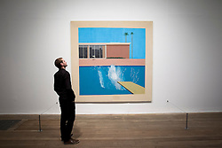 © Licensed to London News Pictures. 13/11/2012. London, UK. A member of Tate Modern staff views David Hockney's 'A Bigger Splash' (1967) at the press view for a new exhibition at the Tate Modern in London today (13/11/12) . The exhibition, 'A Bigger Splash: Painting After Performance', takes a look at the relationship between painting and performance, bringing together the works of over 40 artists, including Jackson Pollock and Cindy Sherman, and runs from the 14th of November 2012 to the 1st of April 2013.  Photo credit: Matt Cetti-Roberts/LNP