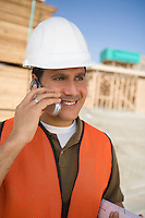 Construction worker standing on construction site and talking in mobile phone