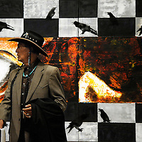 "Former leader of the American Indian Movement, activist and actor Russell Means stands in front of ""I La Lin Kte Lo,"" a painting by Oglala Lakota artist Gerald Cournoyer, in the Center for Western Studies at Augustana College. Means delivered the keynote address during the annual Dakota Conference which focused on the 1973 Wounded Knee occupation."