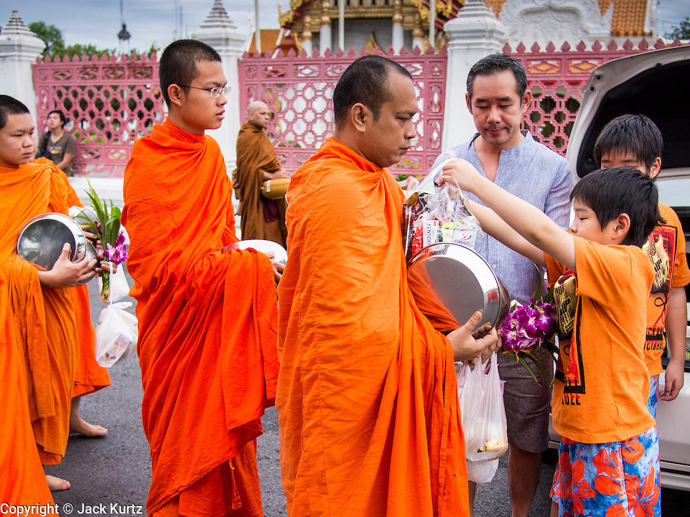 "21 JULY 2013 - BANGKOK, THAILAND:   A family prays with Buddhist monks after making merit at Wat Benchamabophit on the first day of Vassa, the three-month annual retreat observed by Theravada monks and nuns. On the first day of Vassa (or Buddhist Lent) many Buddhists visit their temples to ""make merit."" During Vassa, monks and nuns remain inside monasteries and temple grounds, devoting their time to intensive meditation and study. Laypeople support the monastic sangha by bringing food, candles and other offerings to temples. Laypeople also often observe Vassa by giving up something, such as smoking or eating meat. For this reason, westerners sometimes call Vassa the ""Buddhist Lent.""      PHOTO BY JACK KURTZ"