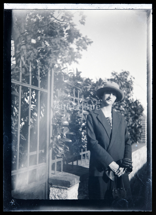 woman standing by metal garden fence France circa 1920s