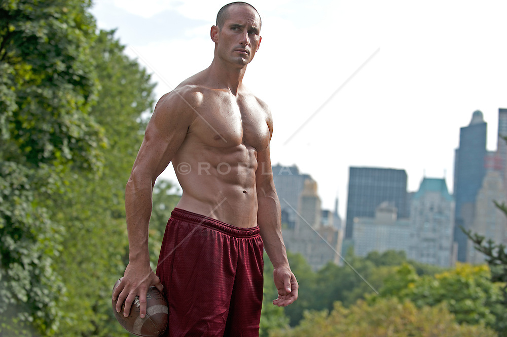 Shirtless Caucsian man holding a football in Central Park