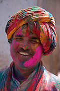 Man covered in coloured paint powder during the festival Holi in Udaipur, Rajasthan, India.