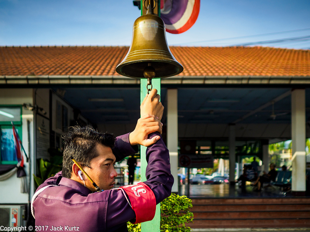 31 MAY 2017 - CHACHOENGSAO, THAILAND: A railway worker rings a bell announcing the departure of a Bangkok bound train at the train station in Chachoengsao, a provincial town about 50 miles and about an hour by train from Bangkok. The train from Chachoengsao to Bangkok takes a little over an hour but traffic on the roads is so bad that the same drive can take two to three hours. Thousands of Thais live outside of Bangkok and commute into the city for work on trains, busses and boats.       PHOTO BY JACK KURTZ