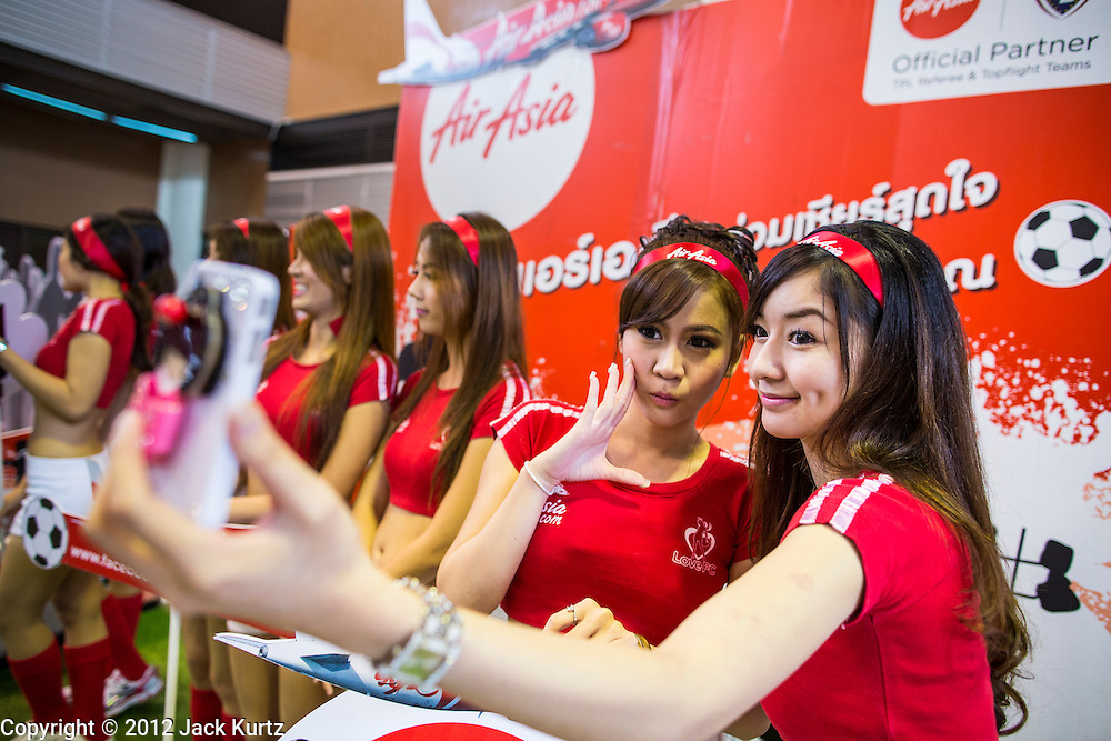 01 OCTOBER 2012 - BANGKOK, THAILAND:  Air Asia spokesmodels greet passengers at Air Asia's reopening of Don Mueang International Airport in Bangkok Monday. Don Mueang International Airport is the smaller of two international airports serving Bangkok, Thailand. Suvarnabhumi Airport, opened in 2006 is the main one. Don Mueang was officially opened as a Royal Thai Air Force base on 27 March 1914 and commercial flights began in 1924. Don Mueang Airport closed in 2006 following the opening of Bangkok's new Suvarnabhumi Airport, and reopened as a domestic terminal for low cost airlines after renovation on 24 March 2007. Closed during the flooding in 2011, Don Mueang was again renovated and reopened in 2012 as the airport for low cost airlines serving both domestic and international passengers. On Monday, Air Asia, Asia's leading low cost airline, transferred all of their flight operations to Don Mueang and the airport was officially reopened. Suvarnabhumi International Airport is already over capacity and Don Mueang's importance as a hub is expected to grow.   PHOTO BY JACK KURTZ