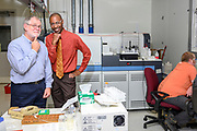 Gaithersburg, Maryland - November 09, 2018: National Institute of Standards and Technology scientists Dr. Robert Vocke, Physical Scientist in the Mass Spectrometry Group, left, and Dr. Savelas Rabb, research chemist, have, right, have used the Avogadro Constant to redefine the mole, using a mass spectrometer (background), a 1kg silicon crystal sphere, and a lot of equations. <br /> <br /> <br /> Scientists at the National Institute of Standards and Technology have helped improved methods for definitively measuring a kilogram. Representatives from 57 countries will vote at the General Conference on Weights and Measures in Versailles, France to redefine four basic units of measurement November 16, 2018. <br /> <br /> CREDIT: Matt Roth for The New York Times<br /> Assignment ID:  30226894A