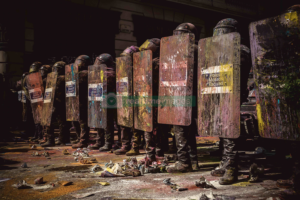 September 29, 2018 - Catalonia, Spain - Catalan riot police agents stand gusrd as they are colored by paint bags thrown from pro-independence activists protesting agsinst s demonstrstion of Police officers of the National Police and Civil Guard marching through Barcelona to pay homage to the participants of last years 'operacion copernico', a massive police deployment within the Catalan secession referendum at October 1st, and to protest for a salary equality with the regional police forces (Credit Image: © Matthias OesterleZUMA Wire)