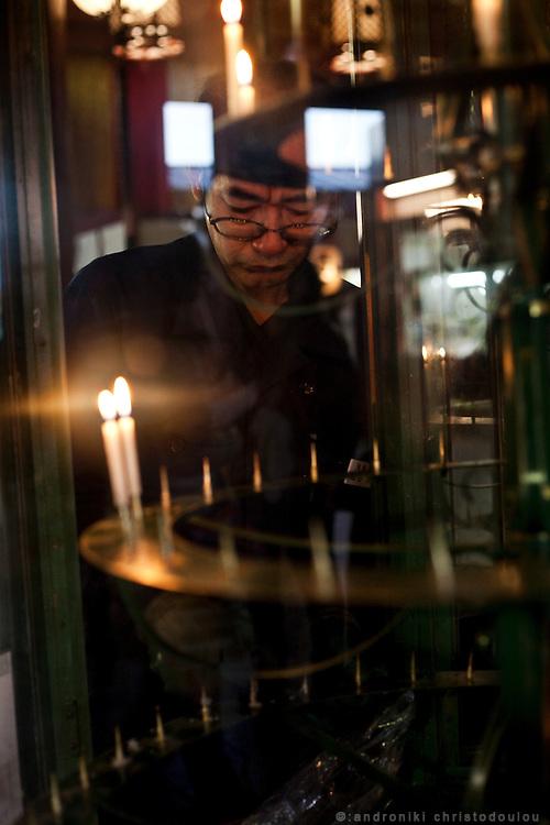 Man cleaning a candle holder in Sensho-ji temple in Asakusa