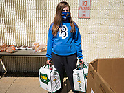 "11 MAY 2020 - DES MOINES, IOWA: GRACE OSTRANDER holds food packages while she waits for clients at a ""no touch"" emergency food pantry at DSM First Church in Des Moines. The emergency pantry at DSM First Church expanded from distribution one day a week to three days per week after the COVID-19 pandemic forced the closure of many Iowa businesses. Food banks and emergency pantries in Iowa continue to see increased demand for services, even though the governor is reopening the state's economy. Iowa's unemployment rate for April hasn't been released yet, but based on national trends, it is expected to soar to well over 10% from 3.8& in March. COVID-19 infections continue to skyrocket. On Monday, 11 May, the governor announced that 12,373 people tested positive for coronavirus (SAR-CoV-2) and  271 had died.             PHOTO BY JACK KURTZ"