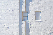 Two vertical shadows on a white wall of a building along The High Line, New York. The High Line is linear park built on an elevated section of a disused New York Central Railroad.