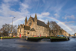 A rainbow over the city of Edinburgh. The rainbow arches over the Mansfield Traquair in the north of the city