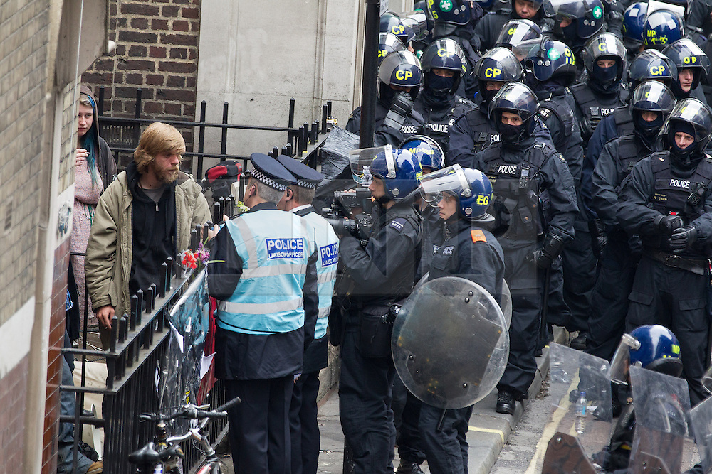 "© Licensed to London News Pictures . 11/06/2013 . London , UK . Police liaison officers talk with occupiers as police surround a former police station on 40 Beak Street , Soho this morning (11th June) which has been occupied by organisers as a base for today's "" Stop G8 "" anti capitalist protest . Demonstrations in London today (Tuesday 11th June 2013) ahead of Britain hosting the 39th G8 summit on 17th/18th June at the Lough Erne Resort , County Fermanagh , Northern Ireland , next week . Photo credit : Joel Goodman/LNP"