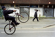 Young teenage boy doing a wheelie on his bike down the road outside housing estate Lambeth Walk South London c.2000