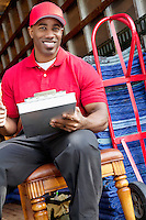 Portrait of a African American delivery man sitting on chair with clipboard