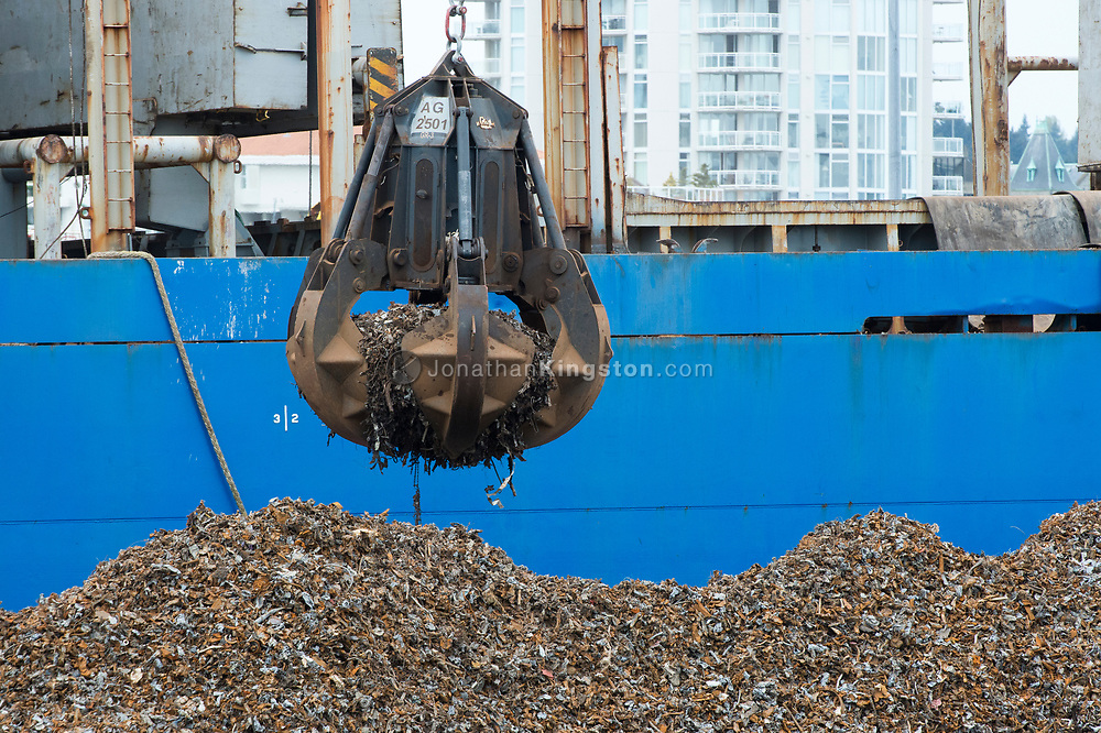 Scrap metal is loaded onto an ocean freighter for recycling.